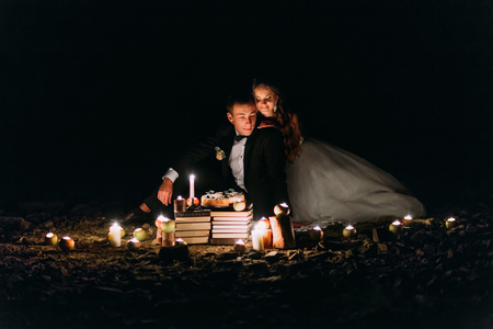Loving couple share a romantic dinner with candles and cake  at beach, coast against wonderful night. Stock Photo