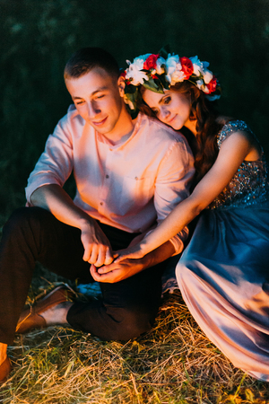 nice guy: Beautiful girl in dress with wreath putting her head on the shoulder of nice guy sitting down outdoors at night.