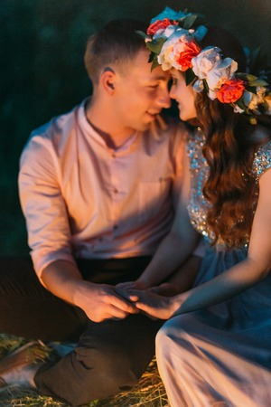 sit down: Beautiful girl in dress with wreath in her hair and nice guy embracing and sit down, lien in the grass at evening.