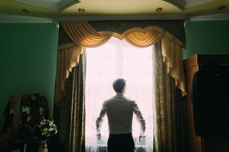 french cuffs: Silhouette of handsome man in white shirt standing near the window.