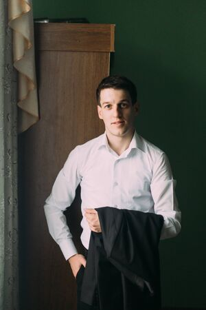 brunete: Brunete man in white shirt with his suit jacket in hands looking at the camera near window.