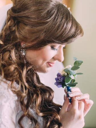 buttonhole: Beautiful bride with long curly hair and veil looking at the buttonhole indoors, close-up.