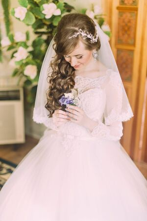 buttonhole: Beautiful bride with long curly hair and veil looking at the buttonhole indoors. Stock Photo