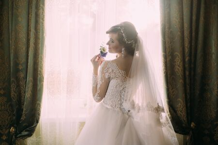 stood: Silhouette of a beautiful bride in a traditional white wedding dress, stood by window holding buttonhole