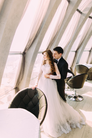 large windows: Just married couple embracing near large windows in luxurious restaurant.