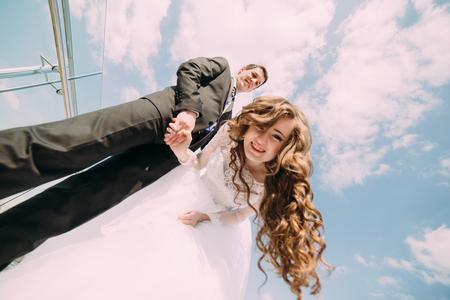 下から見る、青い空の雲に対してカメラのためにポーズ新郎新婦の笑みを浮かべてします。 写真素材
