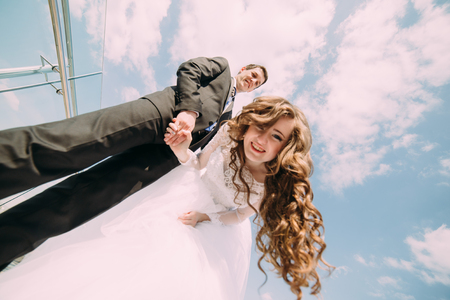 Smiling bride and groom posing for the camera against blue sky with clouds, view from below. Stok Fotoğraf