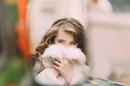 Reflet de jolie jeune femme fermant les lèvres en cape de fourrure dans le rétroviseur.