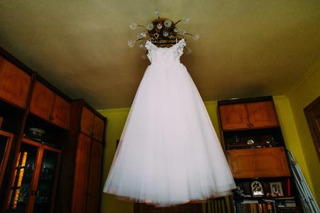lustre: White wedding dress hanging on lustre at hotel room.