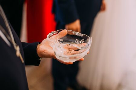 crystal bowl: Mans hand holding heart-shaped crystal bowl with two wedding rings during the ceremony.