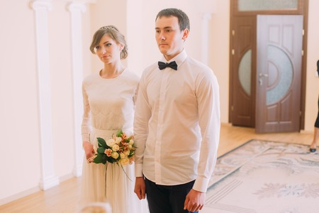 registry: Smiling happy bride with wedding bouquet and groom standing holding hands in hotel or registry office. Stock Photo