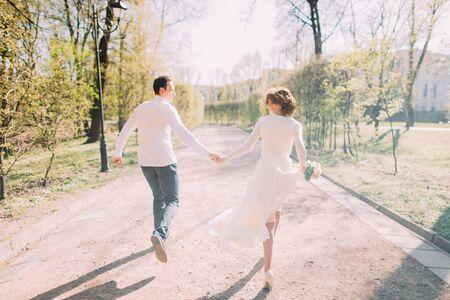 manos unidas: Feliz pareja de boda del novio y de la novia encantadora rubia corredor con las manos juntas en el camino del parque de la ciudad.