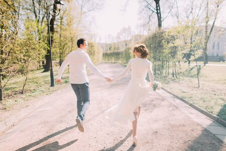 joined hands: Happy wedding couple charming groom and blonde bride running back with joined hands on city park road. Stock Photo
