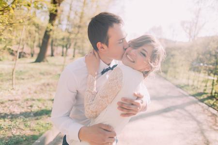 cheek to cheek: Young groom kissing beautiful bride on cheek in spring park.