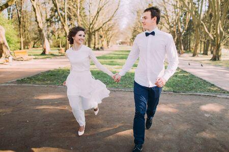 manos unidas: Feliz pareja de boda del novio y de la novia encantadora rubia corriendo con las manos juntas en el camino del parque de la ciudad.