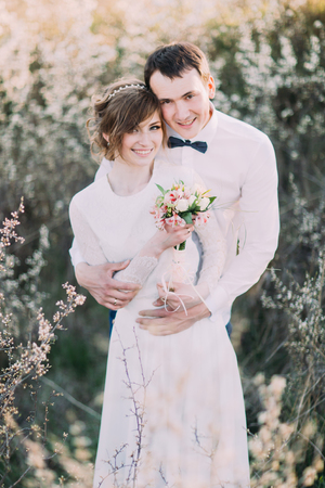 Handsome groom gently holds the bride back holding bouquet in the blossoming spring garden.