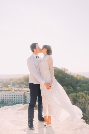 cheerfully: Wedding couple kissing cheerfully at urban landscape background. Bride and groom holding hands, close-up