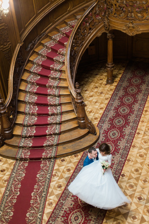 house top: Happy groom carry his wife near big wooden stairs at old vintage house, top view.