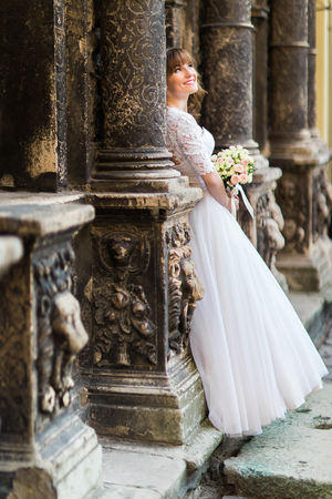towards: Portrait of a beautiful young bride looking towards between the columns of the old building and holding a bridal bouquet. Stock Photo
