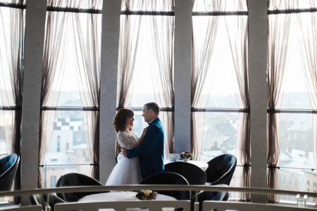fiance: Beautiful bride and fiance in empty restaurant hugging by the windows.