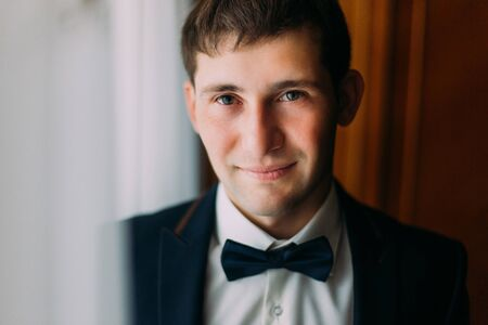 bow window: Handsome brunette man in blue bow tie posing near window, groom morning preparing.