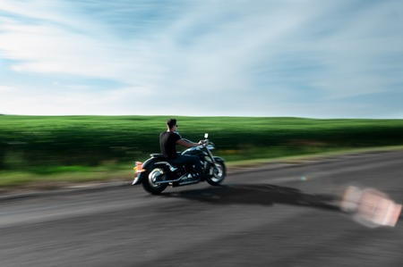 unknown: A view of handsome biker riding unknown motorbike with blur movement, speed concept.
