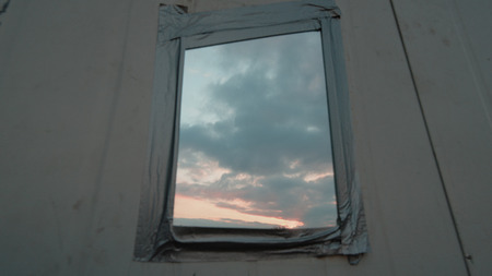 the thrown: Thrown Out Old Mirror Hanging Against Wall With Sky Reflection.