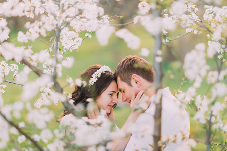 tenderness: Love and tenderness. Beautiful young loving couple embracing in blossom spring garden. Romantic dating.