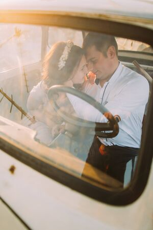 romantics: Portrait of a young girl with floral headband and handsome man sitting in a vintage car and smiling face-to-face. Stock Photo