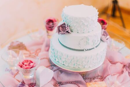 setup man: Blue and white wedding cake decorated with violet flowers. Stock Photo