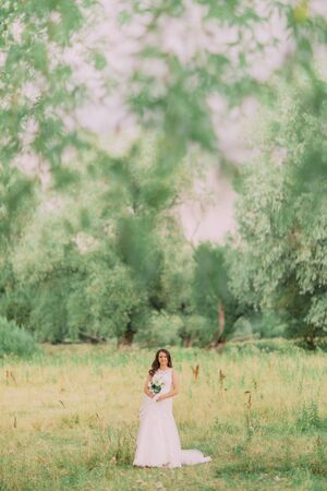 outumn: Luxury stylish young bride on the background of spring sunny green forest. Stock Photo