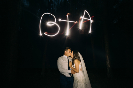 couple lit: Kissing married couple and light painting of their initials on background. Stock Photo