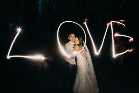 couple lit: Embracing married couple and light painting of the word Love on background.