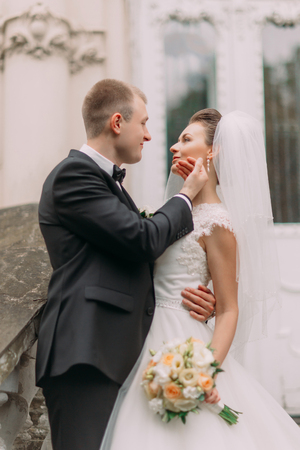 softly: Handsome groom in black suit softly touches brides face. Stock Photo