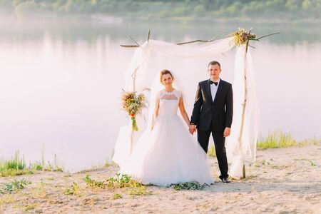 bridegrooms: Beautiful bride in white dress and handsome groom wearing black suit standing under archway on beach wedding ceremony near lake.