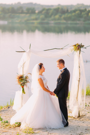 bridegrooms: Beautiful bride in white dress and handsome groom wearing black suit standing holding hands under archway on beach wedding ceremony near lake. Stock Photo