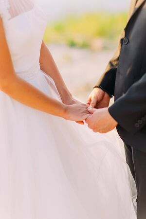 Image of bride and groom holding hands somewhere outside, close-up