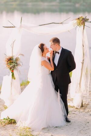 bridegrooms: Beautiful bride in white dress and handsome groom wearing black suit embracing under archway on beach wedding ceremony near lake.