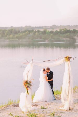 bridegrooms: Beautiful bride in white dress and handsome groom wearing black suit kissing under archway on beach wedding ceremony near lake.