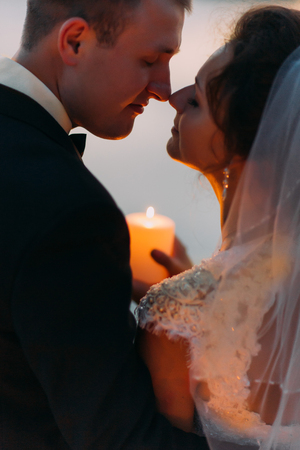 happy moment: Happy bride and groom at moment before kiss holding a candle, close-up.
