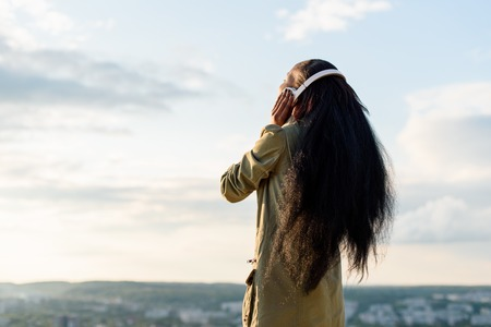 Silhouette of happy smiling young black african american woman with long hair listening to music. Blurred cityscape on background.