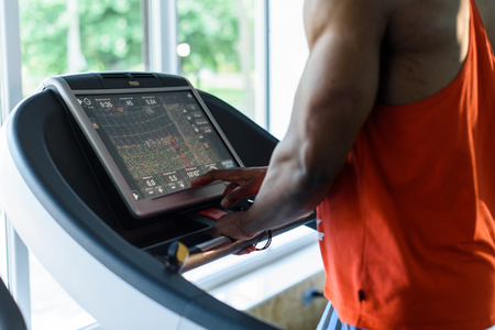 motivations: Muscular handsome black man jogging on a treadmill in the gym.