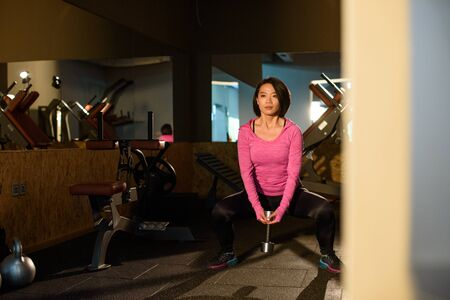 sportwear: Young lovely asian girl in pink sportwear doing exercise with dumbbells at the gym.
