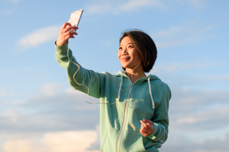 pretty hair: Pretty japanese woman taking selfie outdoor using her phone. Blue cloudy sky background.