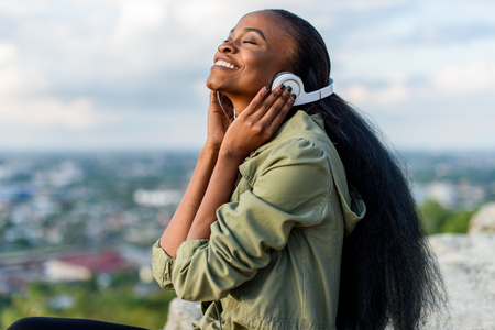 Close-up portrait of happy smiling young black african american woman listening to music. Blurred cityscape on background.