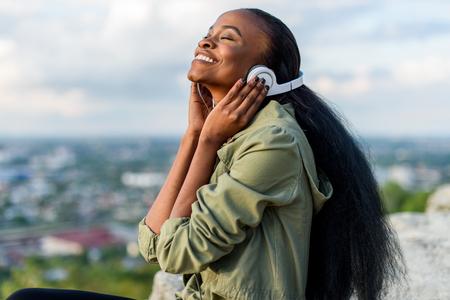 Close-up portrait de sourire heureux jeune noir femme afro-américaine écouter de la musique. paysage urbain flou sur fond. Banque d'images - 57471928