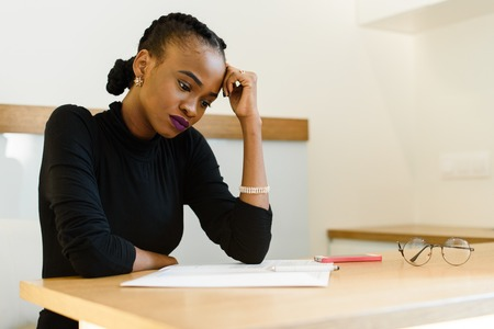 Thoughtful worried African or black American woman holding her forehead with hand looking at notepad in office.