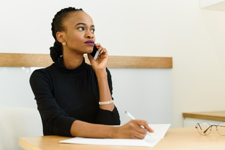 important phone call: Serious confident young African or black American business woman on phone looking away with notepad in office.