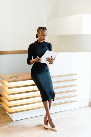 Stern elegant business woman wearing black dress and beige shoes in light office looking at her agenda, full length portrait.