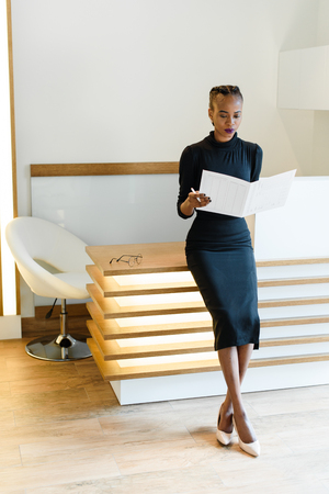 unsmiling: Stern elegant business woman wearing black dress and beige shoes in light office looking at her agenda, full length portrait.